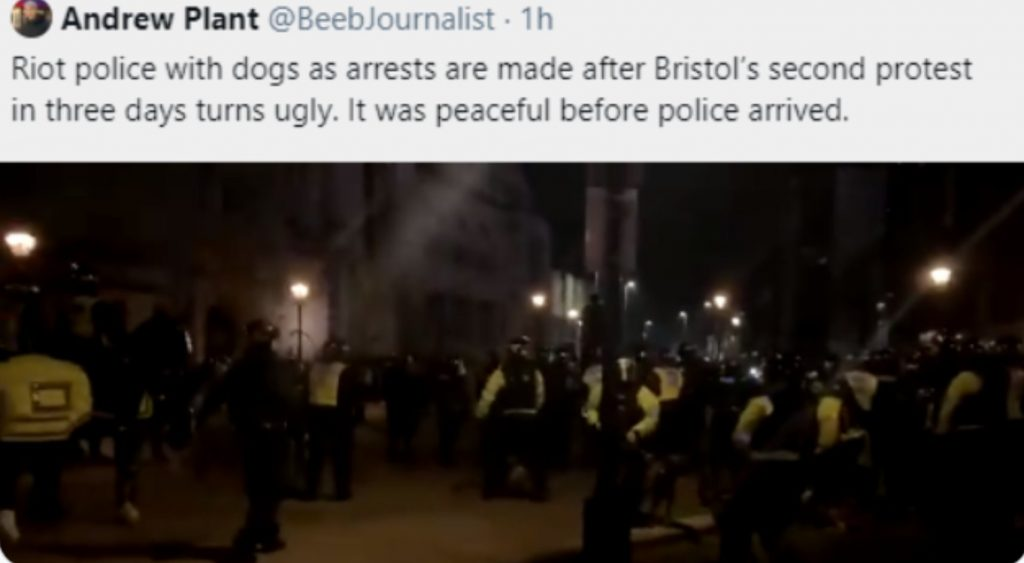 """a tweet by Andrew Plant @BeebJournalist in which he says """"Riot police with dogs as arrests are made after Bristol's second protest in three days turns ugly. It was peaceful before police arrived."""" A preview of the attached video shows a line of riot police."""