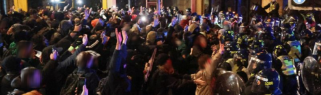 Lines of riot police backed by mounted units push into a crowd of protesters standing with their arms raised
