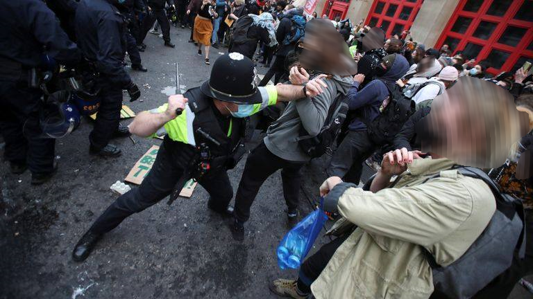 A police officer outside bridewell pushes a protester whilst getting ready to hit them with a baton, the crowd is passive.